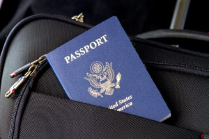 A US passport peaking from a suitcase pocket.