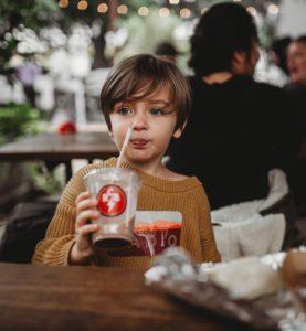 Kid in a restaurant drinking milkshake